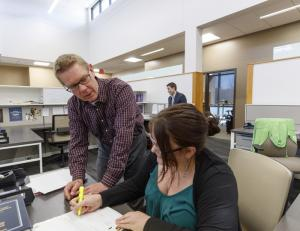 Kevin Ruser and third-year law student Kelsey Heino review a case in the new workspaces of the Marvin and Virginia Schmid Clinic Building.